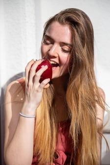 Jonge vrolijke aantrekkelijke vrouw in casual zomerjurk zittend op balkon en het eten van smakelijke sappige rode appel