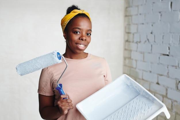 Jonge vrolijke afrikaanse vrouw met een verfroller die in de hoek tegen twee muren staat en je glimlachend aankijkt tijdens de renovatie van het huis