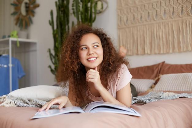 Jonge vrolijke afro-amerikaanse dame met krullend haar, ligt op bed en leest een tijdschrift, geniet van een zonnige vrije dag en glimlacht breed, kijkt dromerig weg en raakt de kin aan.