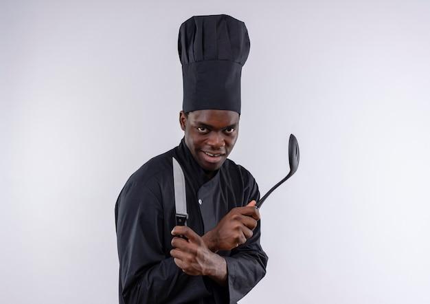 Jonge vrolijke afro-amerikaanse kok in uniform chef houdt mes en spatel op wit met kopie ruimte