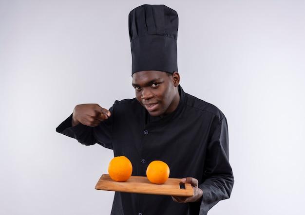 Jonge vrolijke afro-amerikaanse kok in uniform chef houdt sinaasappelen op snijplank op wit met kopie ruimte