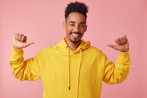 Jonge vrolijke afro-amerikaanse man in gele hoodie, zijn handen omhoog wijzend wijst met zijn duimen naar zichzelf, knipoogt, zegt