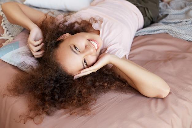 Jonge vrolijke afro-amerikaanse vrouw geniet thuis van de zonnige dag, besteedt haar vrije dag en rust thuis, liggend op het bed en breed glimlachend.