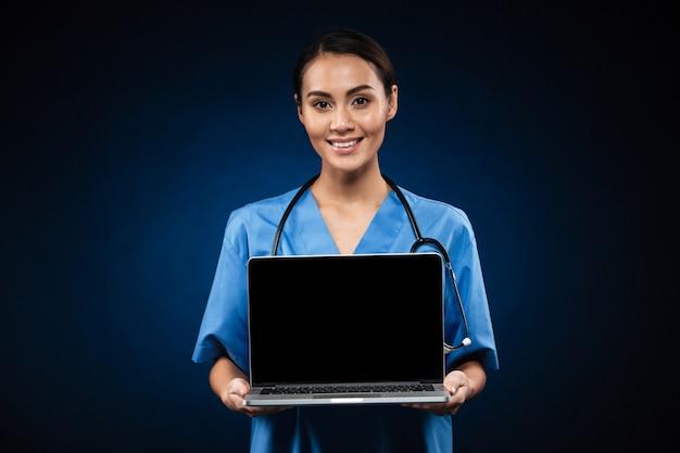 Jonge vrolijke arts die het lege geïsoleerde scherm van laptop computer toont