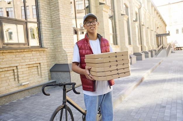 Jonge vrolijke aziatische koerier met dozen met pizza en smilin