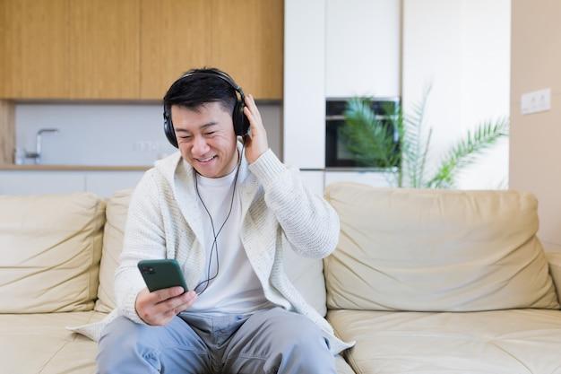 Jonge vrolijke aziatische man die naar muziek luistert in een koptelefoon die thuis op de bank zit
