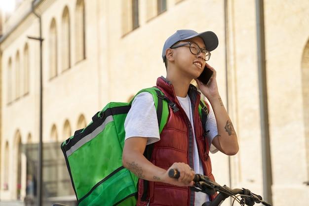 Jonge vrolijke aziatische mannelijke koerier met thermotas die door mob praat