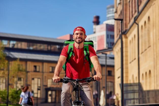 Jonge vrolijke blanke mannelijke koerier met thermotas die voedsel levert aan klanten die op de fiets rijden