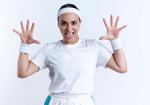 Jonge vrolijke blanke sportieve vrouw met hoofdband en polsbandjes staat met opgeheven handen