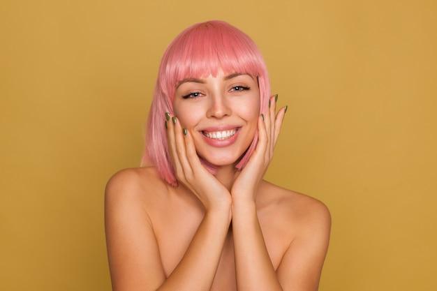 Jonge vrolijke blauwogige rozeharige dame met kort trendy kapsel die positief kijkt met een charmante glimlach en zachtjes gezicht met opgeheven handen aanraakt, geïsoleerd over mosterdmuur