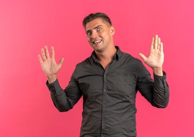 Jonge vrolijke blonde knappe man staat met opgeheven handen geïsoleerd op roze achtergrond