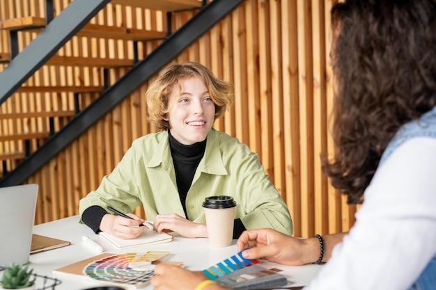 Jonge vrolijke blonde vrouwelijke ontwerper die mannelijke collega met een brede glimlach bekijkt tijdens bespreking van kleuren voor nieuw creatief project