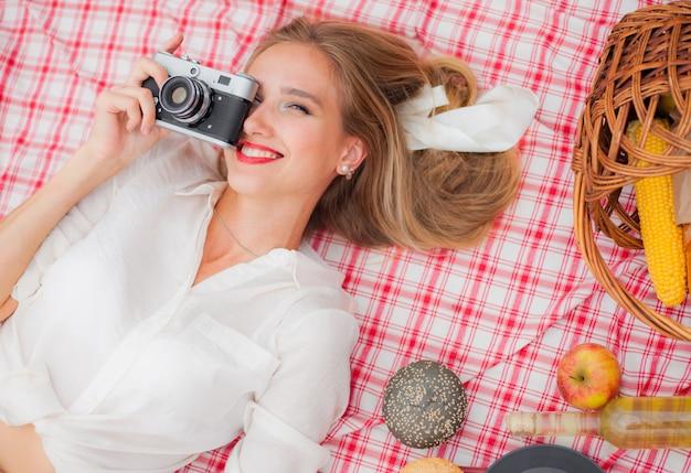 Jonge vrolijke blondevrouw in uitstekende kleren die retro camera houden en foto nemen terwijl in openlucht op picknicktafelkleed ligt. bovenaanzicht