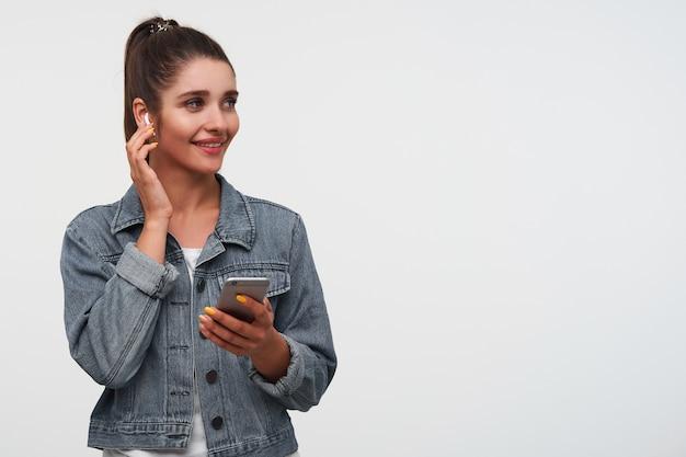 Jonge vrolijke brunette dame draagt een wit t-shirt en spijkerjassen, houdt smartphone en glimlacht in het algemeen, luistert cool lied ant toches nieuwe koptelefoon.