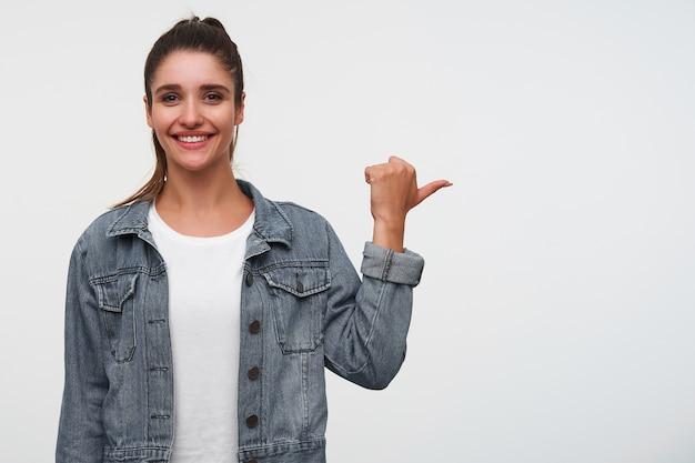 Jonge vrolijke brunette dame draagt in wit t-shirt en spijkerjassen, kijkt naar de camera en glimlacht breed, wijst vingers naar de rechterkant op kopie ruimte, staat op witte achtergrond.