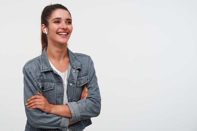 Jonge vrolijke brunette dame met gekruiste armen draagt in wit t-shirt en spijkerjassen, kijkt weg en glimlacht in het algemeen, cool lied luisteren in koptelefoon, staat op witte achtergrond wit kopie ruimte.