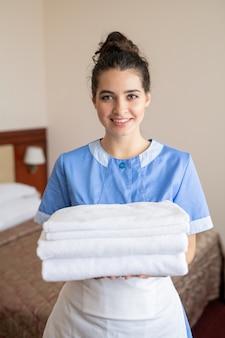 Jonge vrolijke brunette kamer meid met stapel witte schone zachte handdoeken permanent in hotelkamer