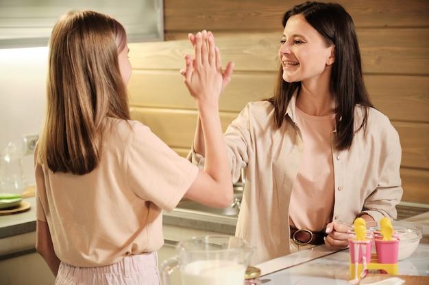 Jonge vrolijke brunette moeder en haar tienerdochter geven elkaar high five terwijl ze bij tafel staan met gevulde siliconen formulieren