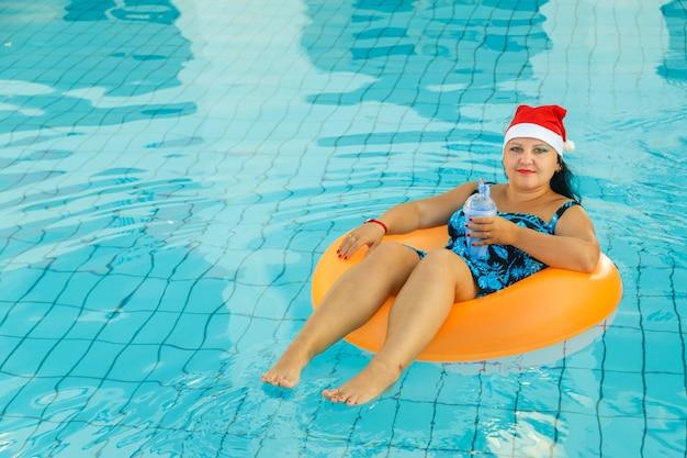 Jonge vrolijke brunette vrouw in santa claus cap in een zwemkring in het zwembad met een cocktail in de hand in de nieuwjaarsvakantie.