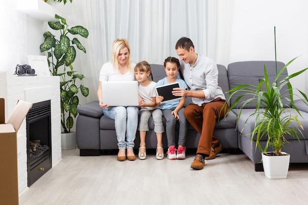 Jonge vrolijke casual familie van twee kinderen en een stel zittend op de bank en kijken naar grappige video's of tekenfilms in touchpad