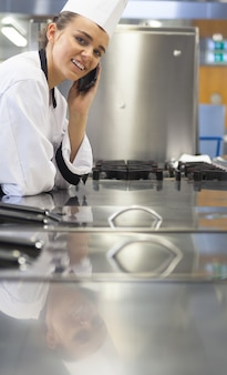 Jonge vrolijke chef-kok die zich naast werkoppervlakte het telefoneren bevindt