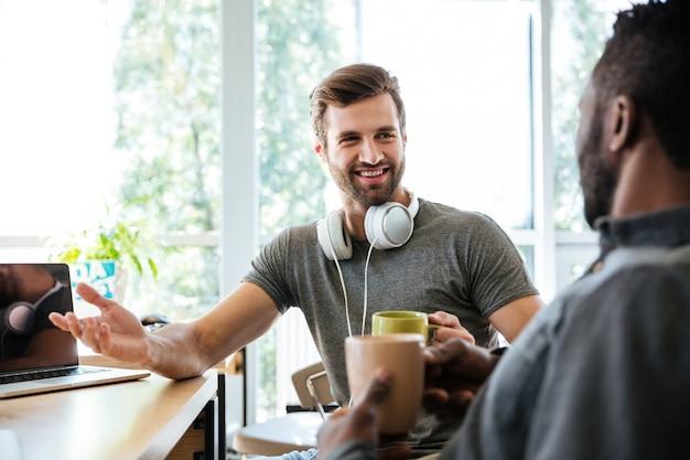 Jonge vrolijke collega's zitten in kantoor naaiatelier
