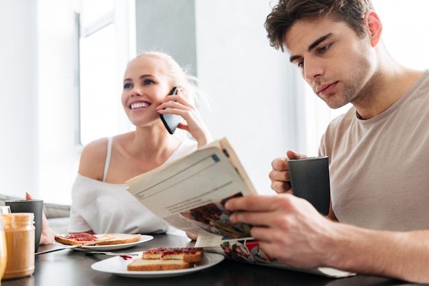 Jonge vrolijke dame die op smarftphone spreekt terwijl haar krant van de mensenlezing
