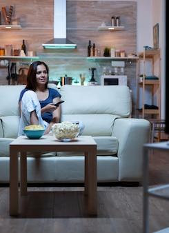 Jonge vrolijke dame die thuis tv kijkt, zittend op een comfortabele bank