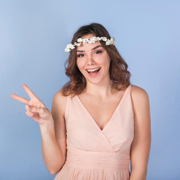 Jonge vrolijke dame met mooie bloemkroon die vredesgebaar toont