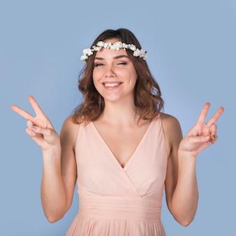 Jonge vrolijke donkerbruine dame met mooie bloemkroon die vredesgebaar toont