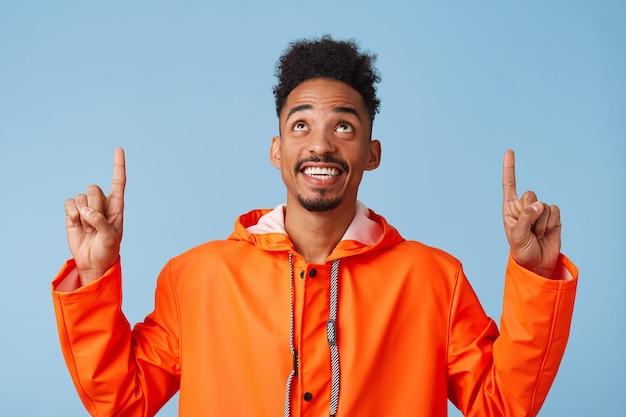 Jonge, vrolijke, donkere aantrekkelijke kerel in oranje regenjas kijkt op en wil je aandacht trekken, wijzende vingers boven zijn hoofd, staat met kopie ruimte.
