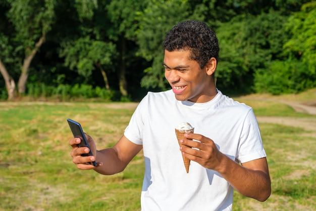 Jonge vrolijke en lachende afro-amerikaanse en blanke man eet ijs en gebruikt smartphone, maakt selfie terwijl hij in de zomer buiten in het park staat