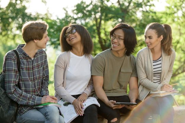 Jonge vrolijke en studenten die in openlucht zitten bestuderen