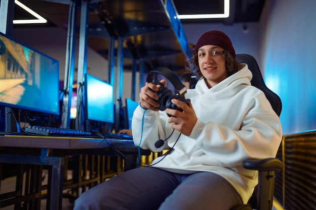 Jonge vrolijke gamer houdt headset vast in gameclub