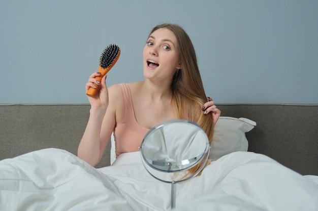 Jonge vrolijke glimlachende vrouw met lang gezond haar in bed met kam en spiegel zitten