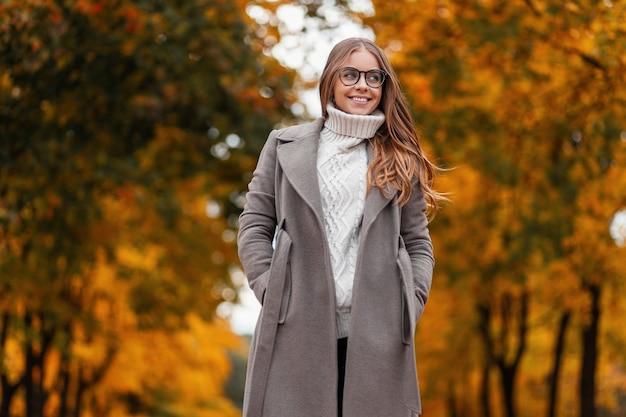 Jonge vrolijke hipster vrouw in elegante lange jas met bril in een gebreide witte trui staat in het park op een warme herfstdag. gelukkig meisje geniet van ontspannen in het bos. seizoensgebonden bovenkleding voor dames.
