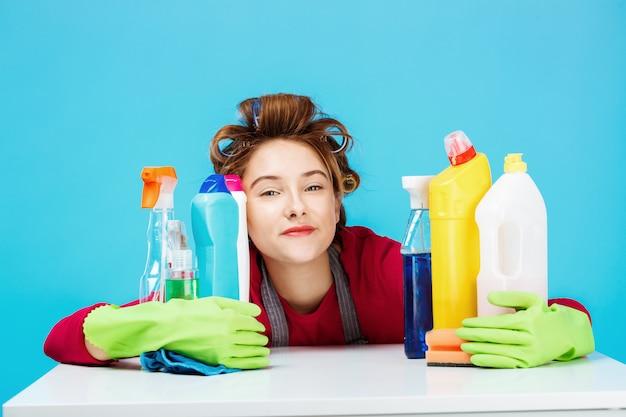 Jonge vrolijke huisvrouw en dagelijkse routine op blauwe muur
