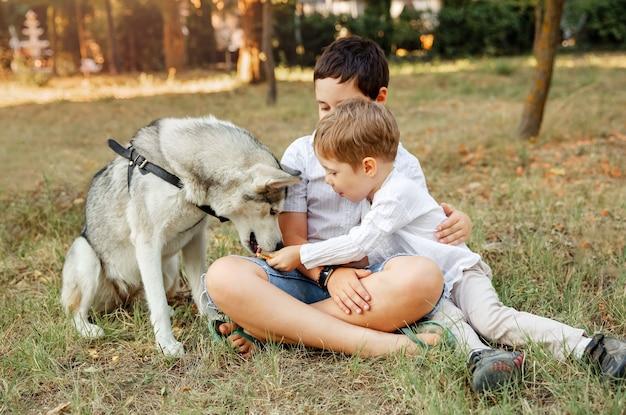 Jonge vrolijke kinderen rusten in de tuin. kinderen spelen met puppy