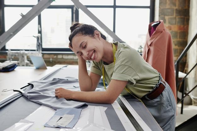 Jonge vrolijke kleermaker of ontwerper van kleding in vrijetijdskleding, leunend op tafel met onafgewerkte jurk, textiel, papieren patronen en liniaal tijdens het werk