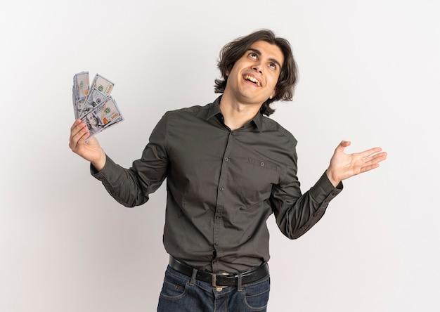Jonge vrolijke knappe blanke man houdt geld en kijkt omhoog geïsoleerd op een witte achtergrond met kopie ruimte