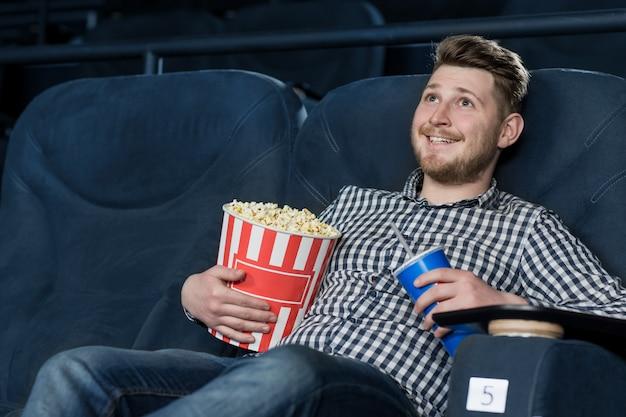 Jonge vrolijke knappe kerel die van een film geniet bij de bioskoop