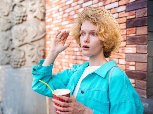 Jonge, vrolijke, krullende roodharige vrouw die een kopje koffie vasthoudt en wordt verrast door bezienswaardigheden