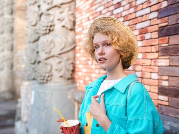 Jonge vrolijke krullende roodharige vrouw in blauwe jas en strohoed reiziger met kopje koffie
