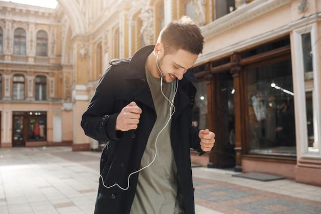 Jonge vrolijke man dansen luisteren naar muziek met een koptelefoon.