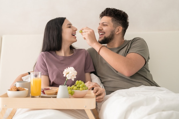 Jonge vrolijke man die druif in de mond van zijn vrouw stopt terwijl hij allebei onder een witte deken in een tweepersoonsbed zit en geniet van het ontbijt