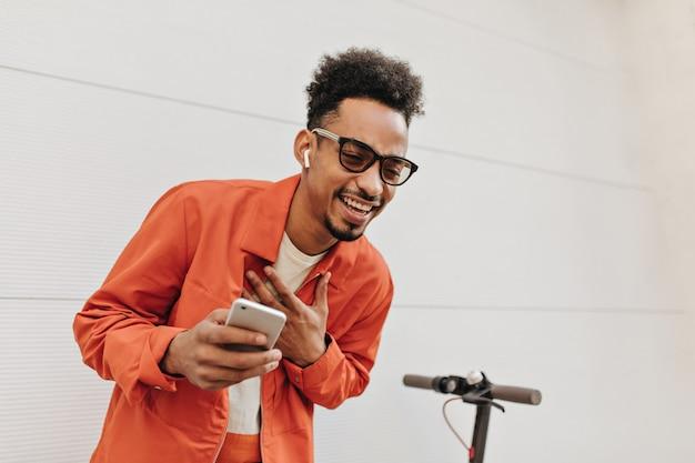 Jonge vrolijke man in oranje jasje, zonnebril en kleurrijk t-shirt lacht en houdt telefoon vast
