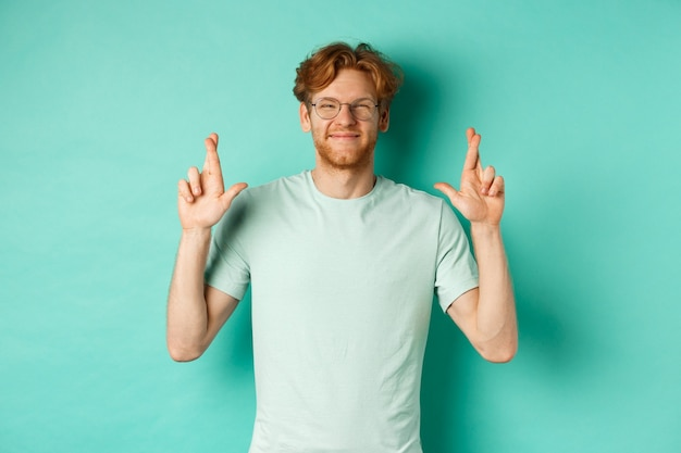 Jonge vrolijke man met rood haar en baard, bril dragen, glimlachen en vingers kruisen voor geluk, wensen doen en er optimistisch uitzien, staande over mint achtergrond