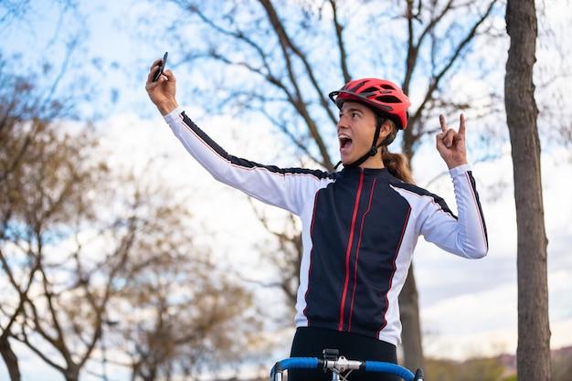Jonge vrolijke mannelijke fietser in sportkleding en helm die handteken tonen en selfie op smartphone in park nemen