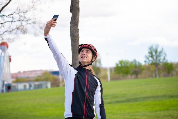Jonge vrolijke mannelijke fietser in sportkleding en helm die selfie op smartphone in park nemen