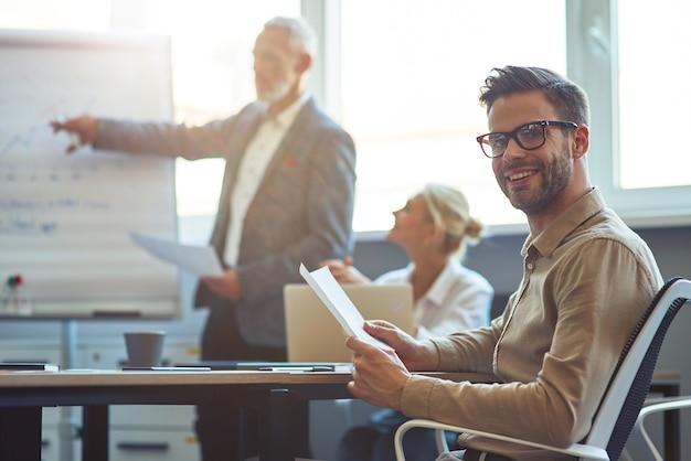 Jonge vrolijke mannelijke kantoormedewerker glimlacht naar de camera terwijl hij een ontmoeting heeft met collega's in de
